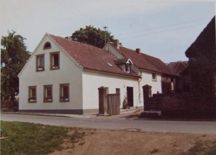 1975 Straßenbau, erster Umbau der Stallung in Wohnraum, Verputz der Außenfassade, Setzen der Rosenstöcke neben der Eingangstür