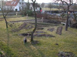 Auf der Wiese werden die Beetbereiche abgemessen und umgegraben